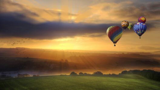 Beautiful golden sunrise glow over fields with hot air balloons flying high