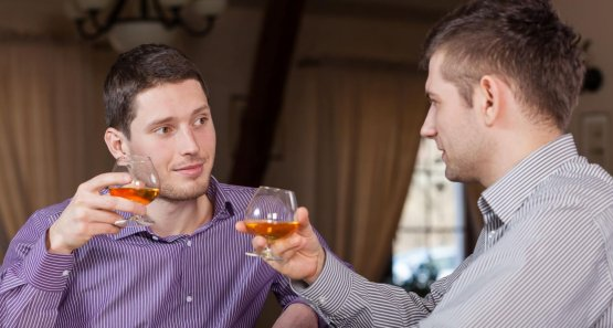 Two businessmen drinking together cognac after work